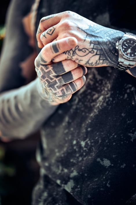 Hände mit vielen Tattoos und einer Uhr
