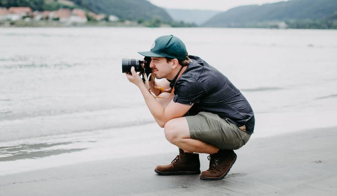 Fotograf an der Donau in den Knien