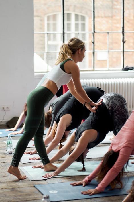 Yoga lehrerin korrigiert die position