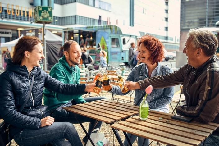 Leute stoßen beim Feschmarkt in Linz mit Getränken an