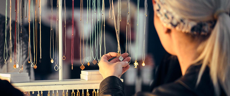 Mädchen sieht sich Halsketten und Schmuck am linzer feschmarkt an