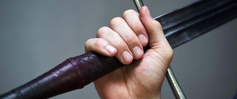 Hand hält einen Schwertgriff fest