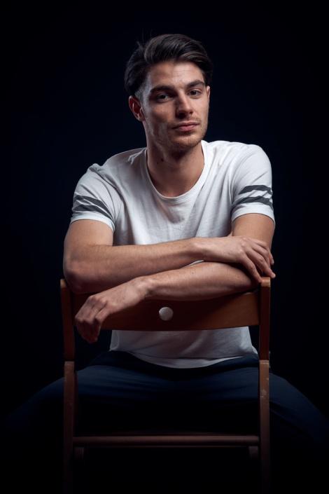 Male Fashion Portrait auf Sessel vor schwarzem Hintergrund
