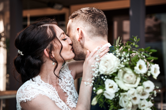 Braut küsst frisch verliebten Gatten auf die wange