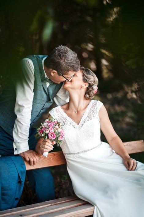 Brautpaar küsst sich im Wald