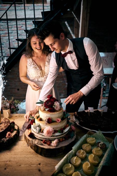 Verliebtes Brautpaar bei HOchzeitsfotoshooting am Rahaberghof schneidet Torte an