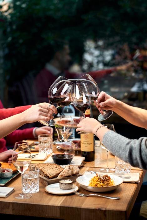 Anstoßen mit Rotwein auf gedecktem Tisch